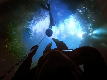 looking upward as a student descends into the beautiful cenote angelita